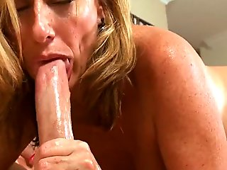 Rubbing oil on her giant tits makes honey very lustful